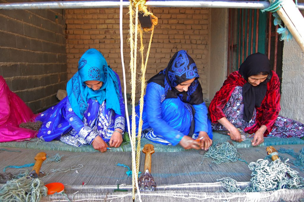 Weavers at work on a horizontal loom, weaving a pile carpet for the Zollanvari company. Fars Province, Iran.